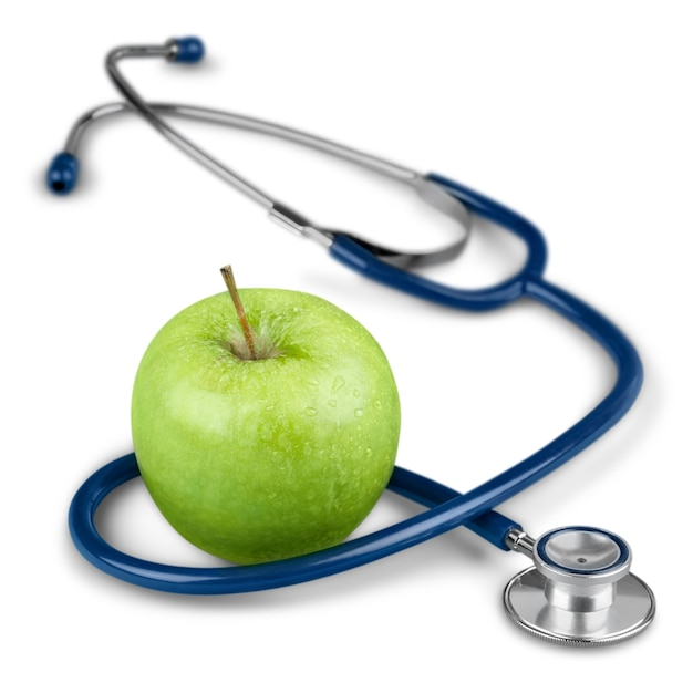 Zielone jabłko i stetoskop na białym tle