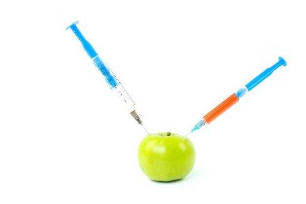 Zielone jabłko i strzykawka na białym tle. koncepcja kosmetologii, pielęgnacji skóry i modyfikacji genetycznych