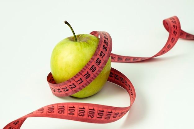 Zielone jabłko i taśma pomiarowa na białym tle