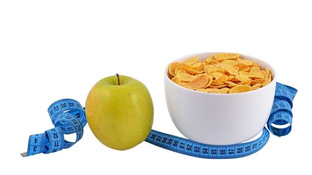 Zielone jabłko, miska płatków kukurydzianych i taśma miernicza na białym tle na w