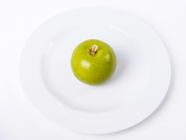 Zielone jabłko na białym talerzu samodzielnie