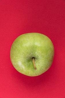 Zielone jabłko na czerwonym tle