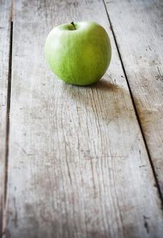 Zielone jabłko na drewnianym stole