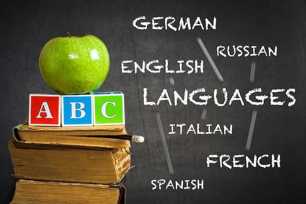 Zielone jabłko na starych książkach na tle tablicy z narysowanym schematem nauki języków