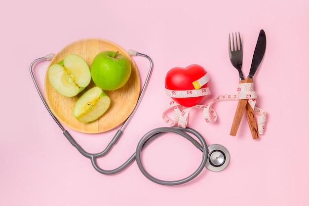 Zielone jabłko na talerzu ze stetoskopem i taśmą pomiarową wokół widelca i noża na białym tle, pojęcie celu odchudzania, cel diety