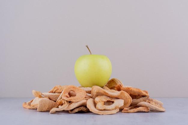 Zielone jabłko siedzi na stosie suszonych plasterków jabłka na białym tle.