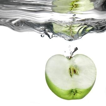 Zielone jabłko spadło do wody z pluskiem na białym tle