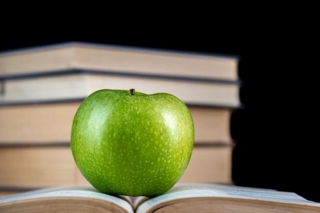 Zielone jabłko spoczywa na książce na czarnym tle. powrót do szkoły