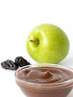 Zielone jabłko, suszone śliwki i tłuczone ziemniaki w talerzu na białym tle na białej powierzchni. składniki na żywność dla niemowląt. zbliżenie.