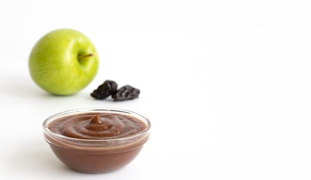 Zielone jabłko, suszone śliwki i tłuczone ziemniaki w talerzu na białym tle na białym tle. składniki na żywność dla niemowląt. skopiuj miejsce.