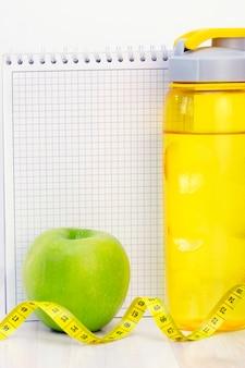 Zielone jabłko, taśma miernicza, bidon i notatnik do pisania na jasnej powierzchni drewnianej. przygotowanie do sezonu letniego i koncepcji plaży, odchudzania i sportu. zdjęcie pionowe