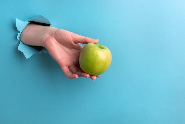 Zielone jabłko w kobiecej dłoni wykonane jest z dziury na turkusowym tle