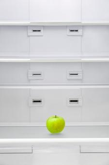 Zielone jabłko w pustej lodówce.