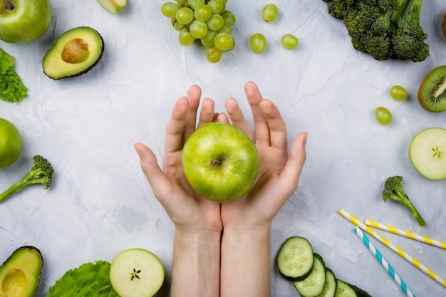 Zielone jabłko w rękach, owocach i warzywach kobiety