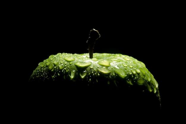 Zielone jabłko z kropli wody na czarno