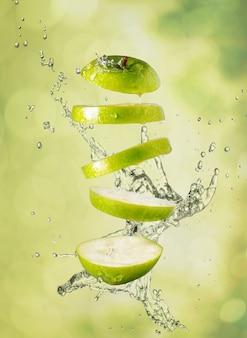 Zielone jabłko z rozpryskami wody w ogrodzie