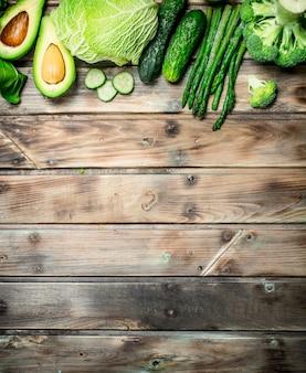 Zielone jedzenie. różnorodność ekologicznych owoców i warzyw na rustykalnym stole.