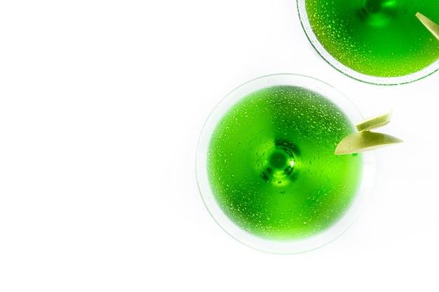 Zielone koktajle appletini w szkle na białym tle na białej powierzchni