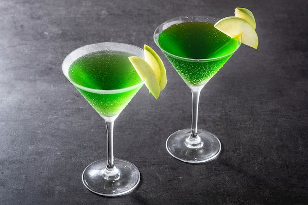 Zielone koktajle appletini w szkle na czarnej powierzchni