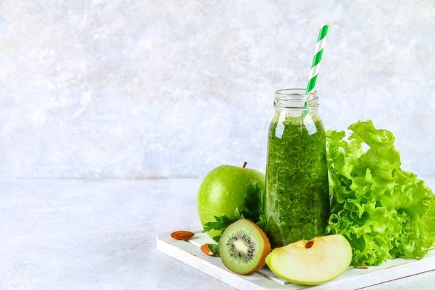 Zielone koktajle z pietruszki, sałatki, kiwi, jabłko w butelce na szarym stole betonowym.