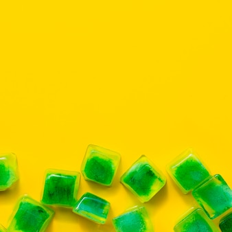 Zielone kostki lodu na żółtym tle