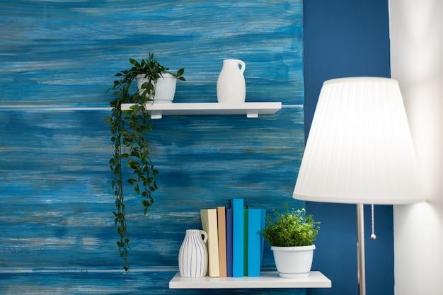 Zielone kwiaty na białej półce w niebieskim pokoju