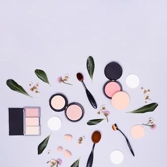 Zielone liście i kwiaty z owalnymi czarnymi pędzlami; gąbka do blendera; kompaktowy puder i paleta cieni do powiek na fioletowym tle