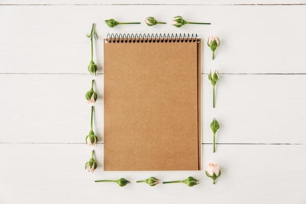 Zielone liście i różowe róże z brązowym notatnikiem pośrodku na białym tle drewnianych desek