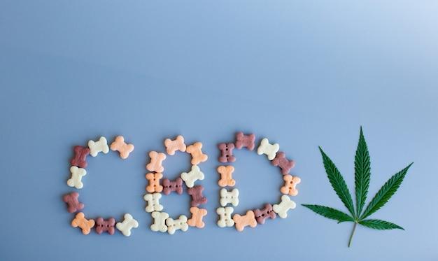 Zielone liście konopi lub konopi oraz napis cbd są napisane z karmy dla zwierząt domowych