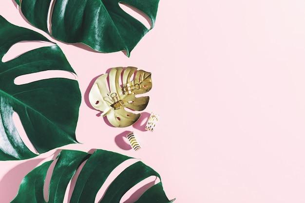 Zielone liście monstera z rekwizytami biurowymi na różowym tle