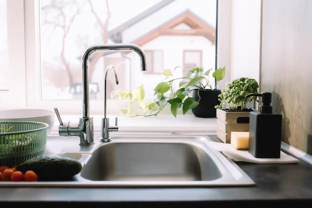 Zielone liście sałaty, ogórek i pomidor w kuchni w zlewie gotowe do mycia.