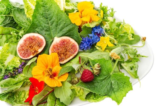 Zielone liście sałaty z figami i jadalnymi kwiatami ogrodowymi. zdrowe odżywianie detoksykacyjne