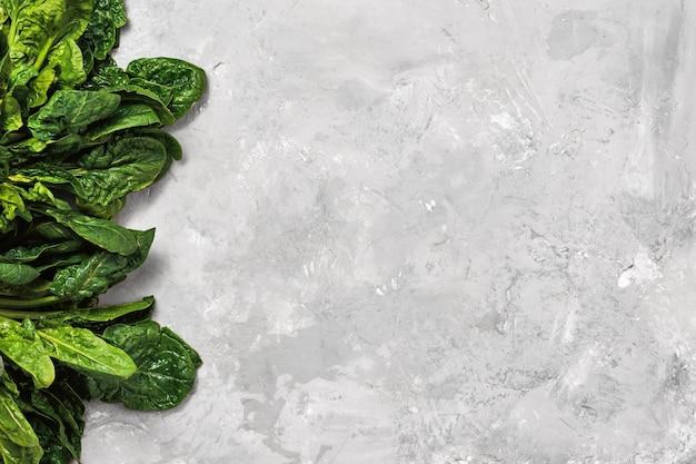 Zielone liście świeżego szpinaku w neutralnej szarości