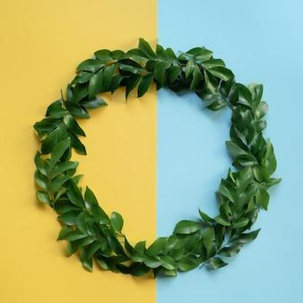 Zielone liście tworzą okrąg z jasnożółtym i niebieskim tłem oraz cieniami słońca