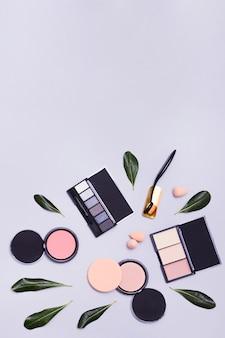Zielone liście z owalnym pędzlem do makijażu; paleta cieni do powiek i kompaktowy puder na fioletowym tle