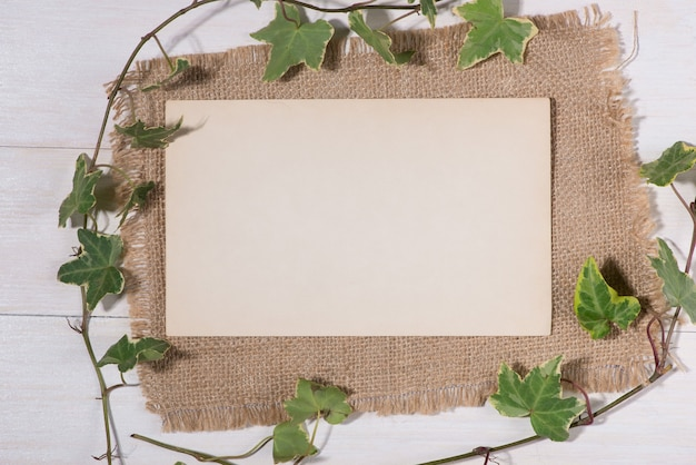 Zielone liście z pustą etykietą i papierem na drewnianym tle