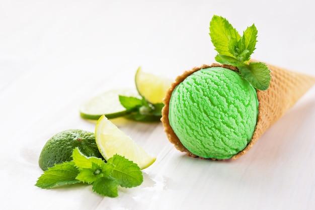 Zielone lody w rożku waflowym z listkami limonki i mięty