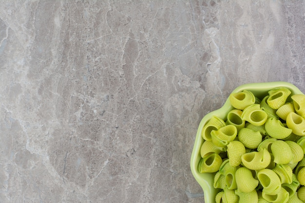 Zielone makarony domowej roboty na talerzach na szarym polu.