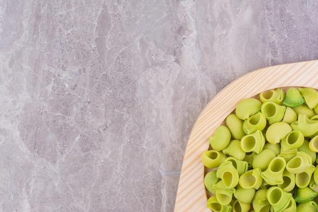 Zielone makarony w drewnianym talerzu na marmurze