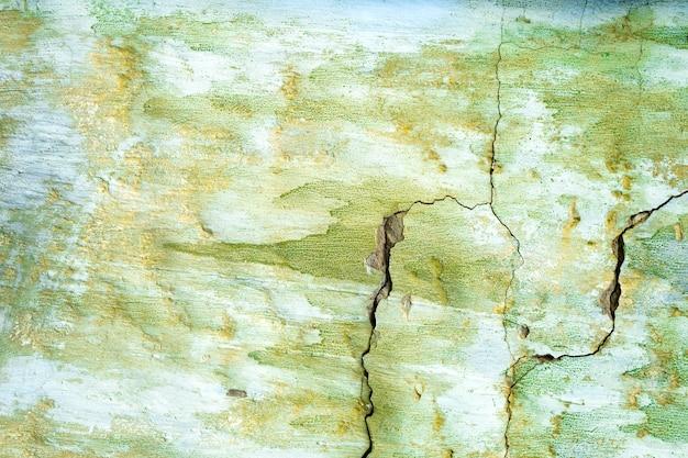 Zielone malowane uszkodzone tło ściany grunge lub tekstury