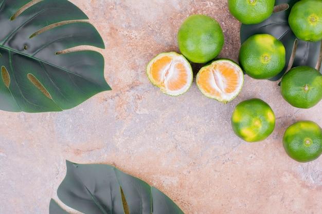 Zielone mandarynki na białym tle na marmurze.