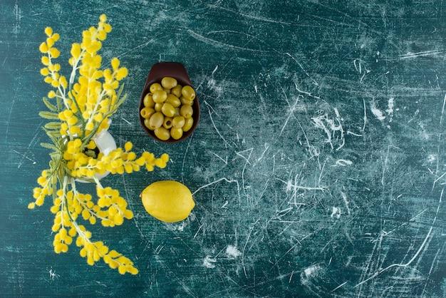 Zielone marynowane oliwki w czarnej filiżance z dodatkiem cytryny. zdjęcie wysokiej jakości