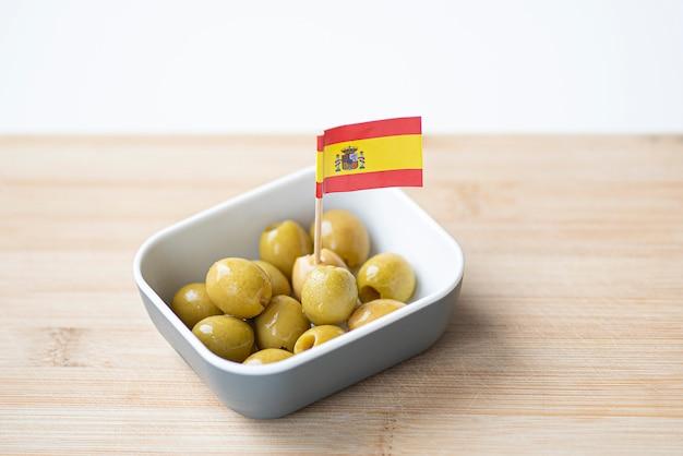 Zielone marynowane oliwki w plastikowej misce z hiszpańską flagą z papieru