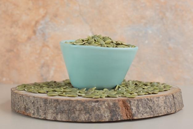 Zielone nasiona dyni w pojemniku na betonie.
