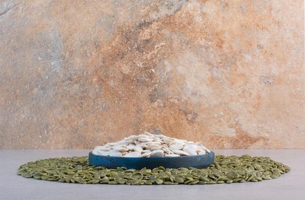 Zielone oczyszczone i białe nasiona dyni na betonowym tle.