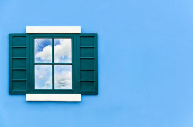 Zielone okno dom otwarte, aby odzwierciedlić niebo lato i biała chmura na lustrze na niebieskiej ścianie na zewnątrz, stare drewniane okna rama domu włochy klasyczny styl vintage kopia przestrzeń dla tła