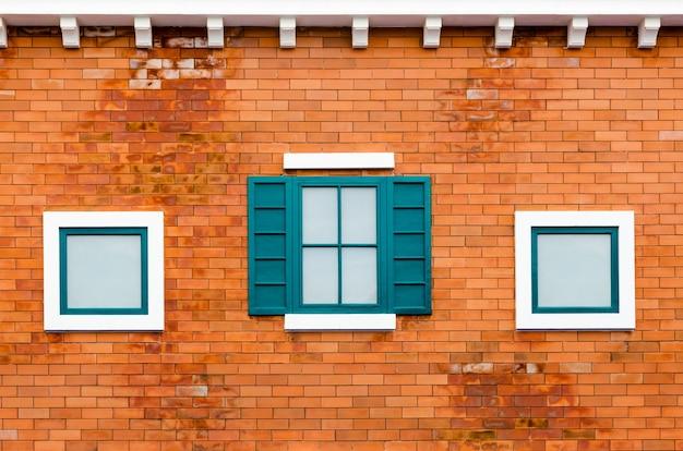 Zielone okno na pomarańczowym ceglanym murze na zewnątrz domu we włoskim stylu retro