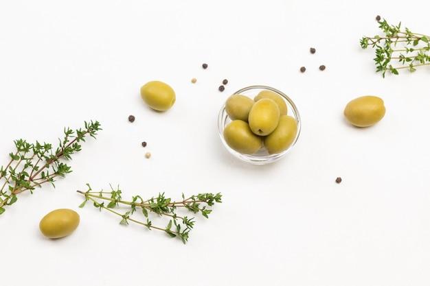 Zielone oliwki i gałązki tymianku na białym stole. leżał na płasko.