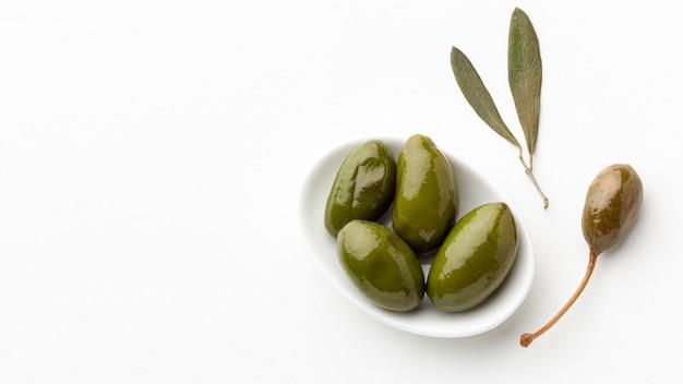 Zielone oliwki na talerzu z liśćmi z kopii przestrzenią