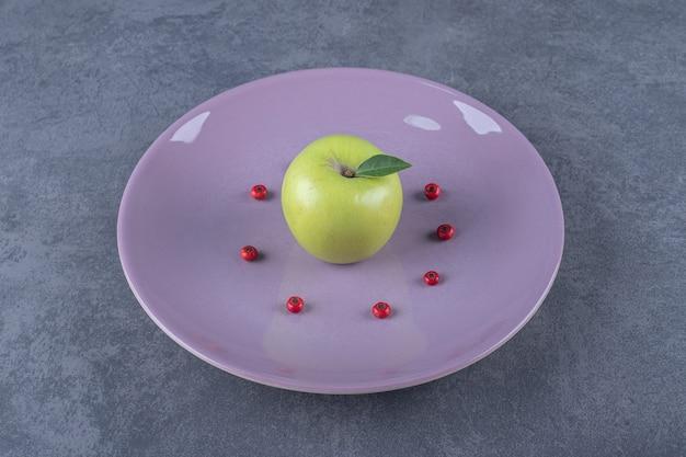 Zielone organiczne świeże jabłko na fioletowym talerzu.
